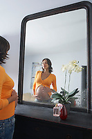 Pregnant woman admiring stomach in bedroom mirror