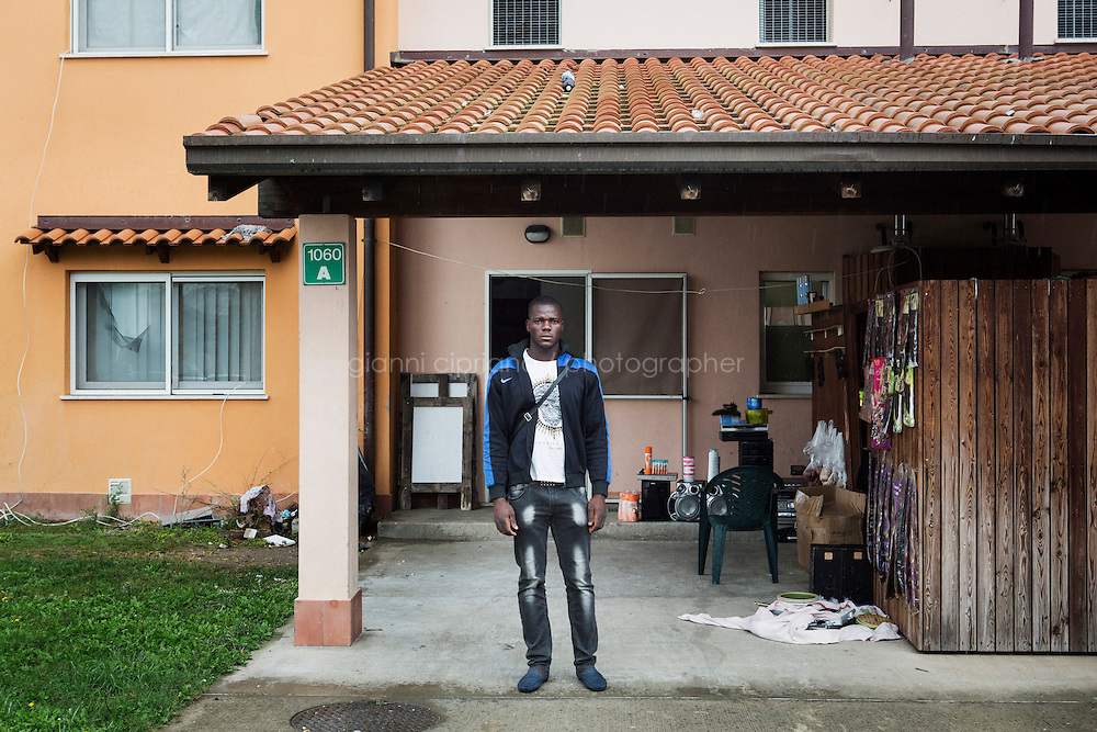 MINEO, ITALY - 26 NOVEMBER 2014: Francis Ibizugne, a 25 years old asylum seeker from Nigeria, poses in front of the house he shares with other 7 asylum seekers at the CARA (Accommodation Centre for Asylum Seekers) in Mineo where approximately 4,000 asylum seekers live, in Mineo, Italy, on November 26th 2014. Francis was rescued on a boat carrying 750 asylum seekers from Ghana, Gambia, Nigeria, Syria and Pakistan on April 9th, 2014, after 11 hours in the Mediterranean Sea. He left Nigeria in 2009, then lived and worked in Libya for 13 months as a mechanic. He left Libya after his safety was theathened and was shot in a leg. Three times a week, Francis trains as a boxer in a gym in Ramacca, a Sicilian village 15km away from Mineo.<br /> <br /> By law, asylum-seekers can be held for 35 days in a CARA. In reality, the average stay is closer to a year.The Cara is located at the &quot;Residence degli Aranci&quot; (Residence of the Oranges), a small town built to accomodate the families of US soldiers operating at the Naval Air Station of Sigonella 40km away. Since 2011 the &quot;Residence degli Aranci&quot; hosts the Accommodation Center for Asylum Seekers, which has since then hosted more than 12,000 seekers of 47 nationalities and over 200 ethnic groups. The CARA of Mineo includes 404 houses. Each housts from 7 to 11 asylum seekers.