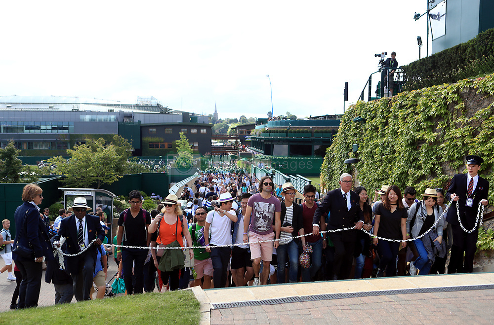 Spectators are led up to Murray Mound at the start of day two of the Wimbledon Championships at The All England Lawn Tennis and Croquet Club, Wimbledon.