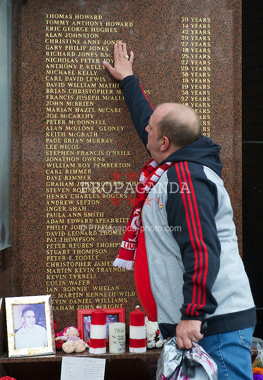 LIVERPOOL, ENGLAND - Sunday, September 23, 2012: A supporter touches the name of a victim of the Hillsborough Stadium Disaster at Liverpool's Hillsborough memorial before the Premiership match against Manchester United at Anfield. The release of the Hillsborough Independent Panel's report shed light on one of the biggest cover-up's in British history which sought to deflect blame from the Police onto the Liverpool supporters. (Pic by David Rawcliffe/Propaganda)