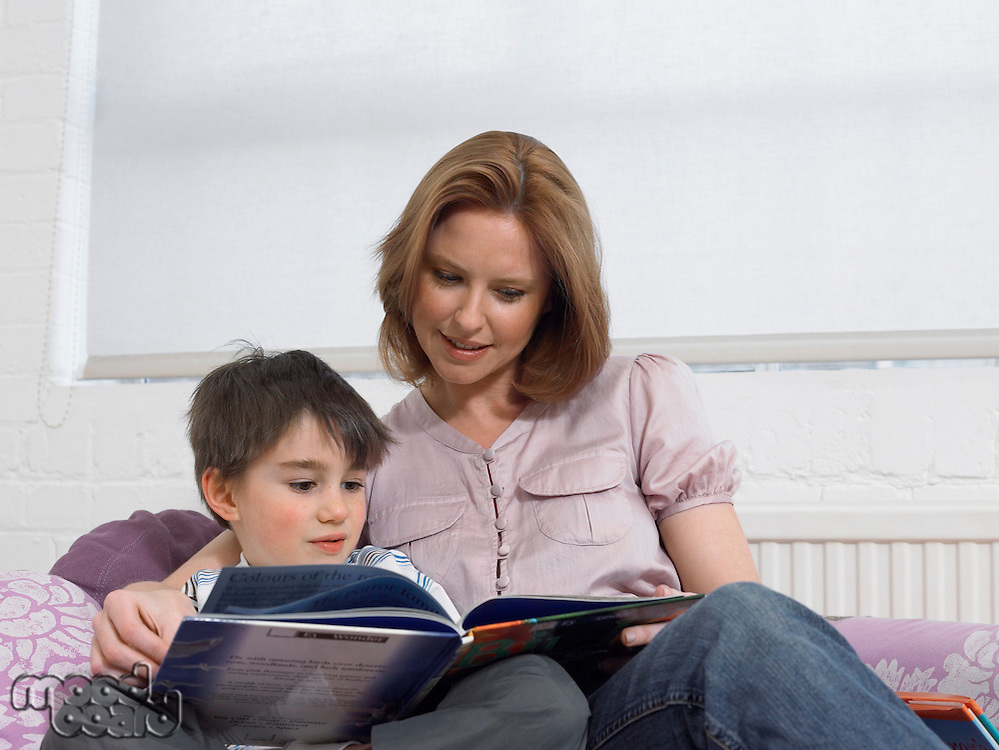 Mother and son (5-6) reading book on couch in living room