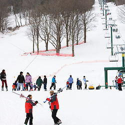 A man and woman head to the slopes at the Quechee Ski Hill in Quechee, Vermont. Model Release.