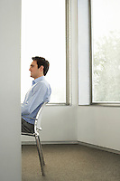 Businessman sitting on chair in office side view half length