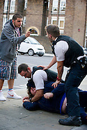 A young man uses his mobile phone to film two policemen as they wrestle his friend to the floor in Chapel Market, Islington, London. The officers mistakenly accused the young man of carrying a knife and forced him to the ground despite his pleas of innocence. As it turned out they had the wrong person and he was released.