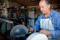 """Avigliano (PZ), 04-10-2010 ITALY - Vito Aquila, artigiano di Balestre. Il coltello di Avigliano, comunemente conosciuto come """"balestra"""", impreziosito con decorazioni in argento e ottone che le conferivano un certo valore non solo artistico,ha identificato per tutto l'Ottocento e parte del Novecento il carattere fiero e risoluto del popolo aviglianese, come attestato in una lunga casistica di riscontri documentari. La """"balestra"""" è un'arma a tutti gli effetti, ed è già considerata -nell'ambito delle manifatture di ferro - oggetto di pregio. Per l'approvvigionamento dell'argento e dell'ottone destinati alla decorazione del manico del coltello gli armieri si rivolgevano agli orefici o agli ottonari. La """"balestra"""" era un'arma del popolo, pronta ad essere impiegata, a seconda delle circostanze, per la difesa o l'offesa tanto dagli uomini quanto dalle donne. Queste, la ricevevano come regalo di fidanzamento dal rispettivo promesso sposo per meglio difendere il proprio onore, perpetrando un'usanza molto sentita almeno fino ai primi decenni del '900..Nella Foto: Lavorazione della lama."""