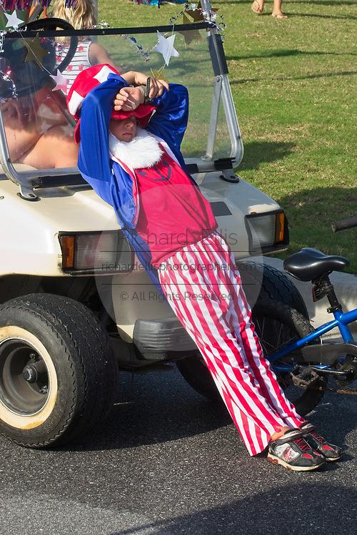 A young boy dressed as Uncle Sam rests in 90-degree heat during the annual Sullivan's Island Independence Day parade July 4, 2017 in Sullivan's Island, South Carolina. The tiny affluent sea island hosts a bicycle and golf cart parade through the historic village.