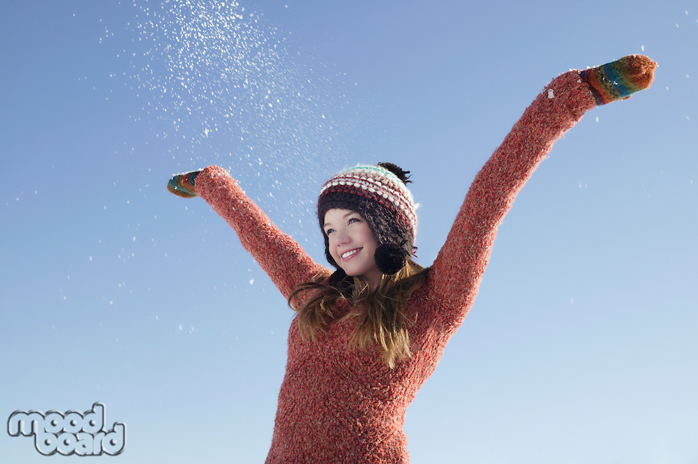 14 year old girl in winter clothing with arms raised
