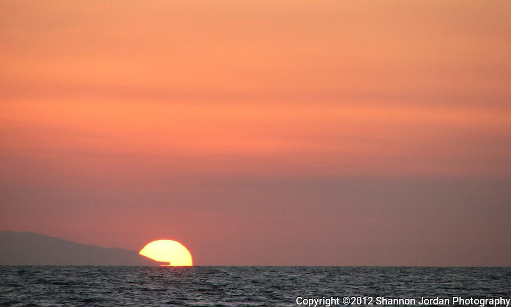The sun sets behind the west end of Santa Cruz Island off the coast of Santa Barbara, California.