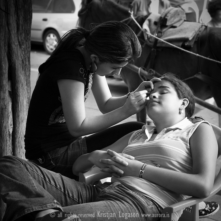 Young woman plucking the eyebrows of an other at the square in Juayua during the festive events of fiesta gastronomica