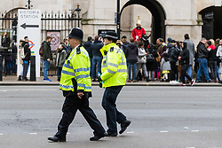London, December 31 2017. Police in high visibility jackets and numerous anti-terrorism and crowd control measures are in place in the capital ahead of the New Year's Eve fireworks and revelry in central London. PICTURED: Two police officers patrol along Whitehall opposite Horseguards. © SWNS