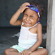 Crying unhappy papuan kid.