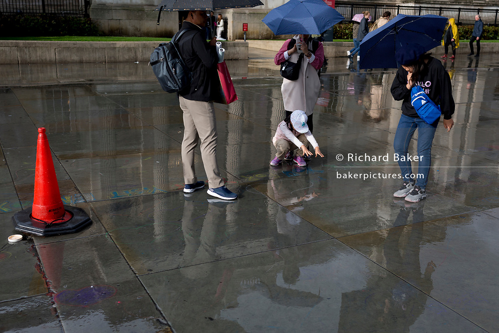 A young visitor riholds out her hands to see their reflection on the pavement after a heavy autumnal downpour in Trafalgar Square in central London, on 1st October 2019, in London, England.
