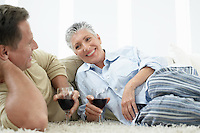 Couple drinking wine on rug in home