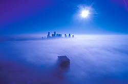 Aerial view of the tops of downtown Houston, Texas skyscrapers above a blanket of fog at dawn.