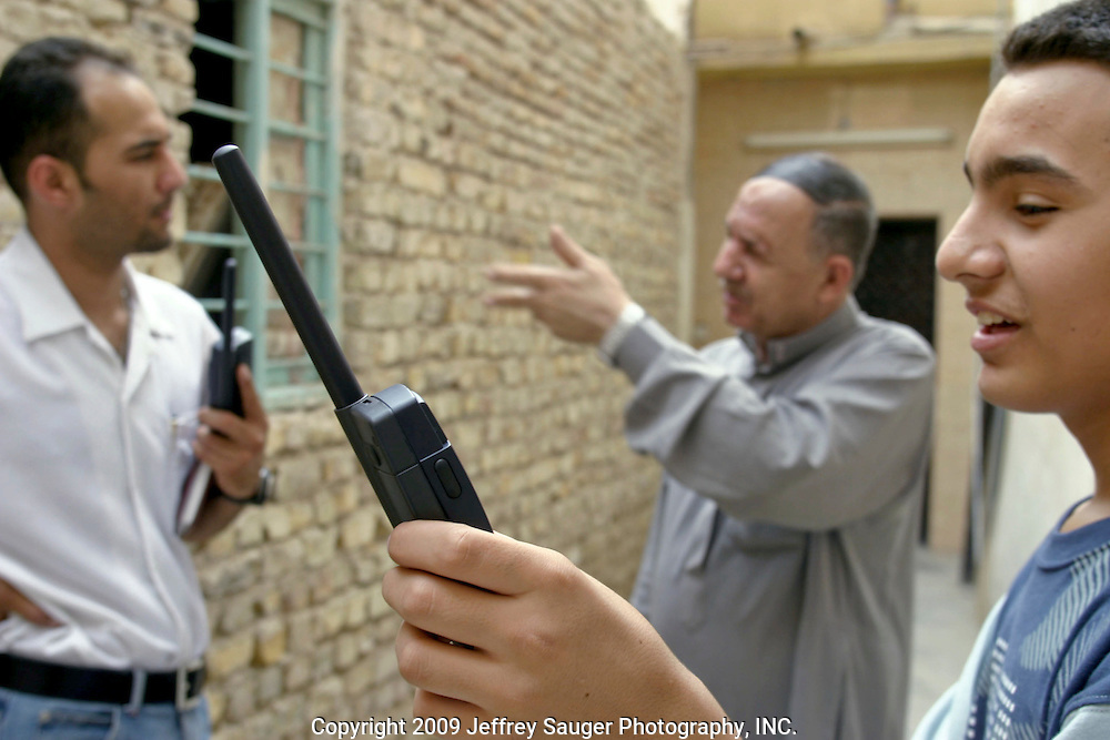 In a constant battle to find a good connection, Emad Al-kasid, his father Malik and brother Hussein talk outside their apartment with their satellite phones in Karbala, Iraq, Monday, July 21, 2003. ..The family is travelling back to its home city of Nassiriyah, Iraq, for the first time since 1991 after fighting in the failed uprising against Saddam Hussein, fleeing to a refuge camp in Saudi Arabia for 3 years and finally settling in Dearborn, MI.