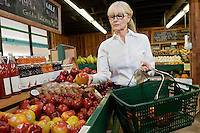 Senior woman shopping for apples in market