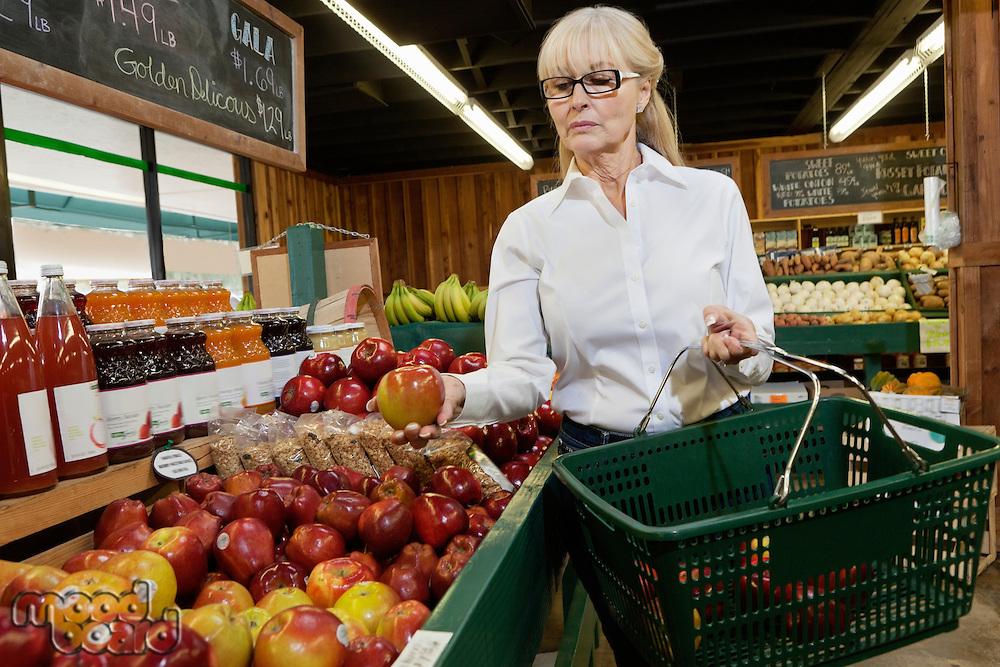 Senior woman shopping for apples in market