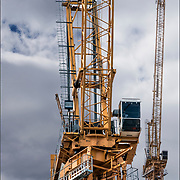 Two images(close up and long view) of tower crane on top of skyscraper under construction.<br /> <br /> Two or more layers were used.