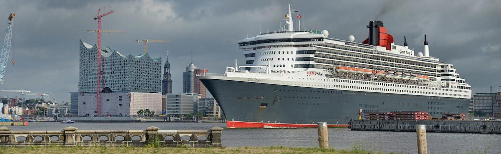 Passagierschiff Queen Mary 2 läuft in den Hamburger Hafen ein, vorbei an der Elbphilharmonie und Michel im Hintergrund