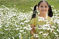 Girl (7-9) holding flowers in meadow portrait