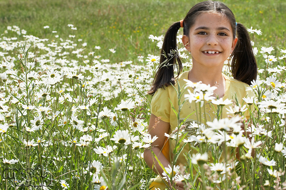 Girl (7-9) holding flowers in meadow portrait