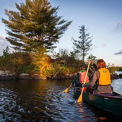A young couple paddles a canoe on Long Pond in Maine's north woods. Near Greenville, Maine.