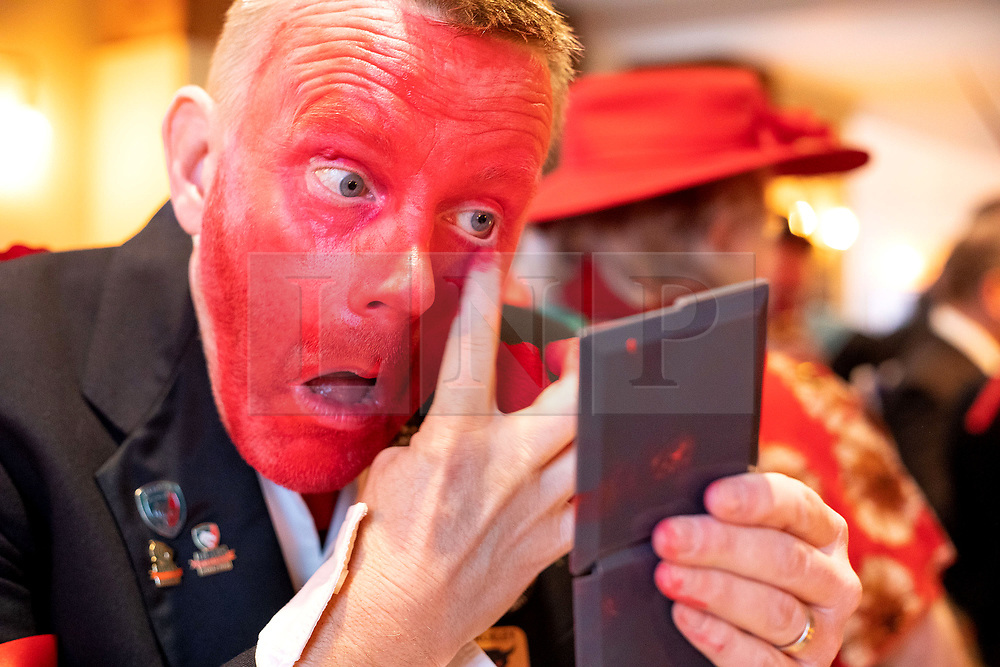 """© Licensed to London News Pictures. 11/01/2020. Sharnford, Leicestershire, UK. Plough Tour. The Hinckley Bullockers taking part in their annual plough tour. Pictured, Steve Robinson applies the red pigment to his face in preparation for dancing the Plough Tour. Painting their faces red they dance and pull a decorated plough through villages in Leicestershire. The picture shows them performing in Sharnford where they play and dance outside two public houses before moving on to other villages finishing at the end of the day. Traditionally the plough was prepared for the new season, dressed in gaudy ribbons and taken in procession around the villages. In South West Leicestershire the men pulling the plough, who """"raddled"""" their faces with red dye thought to be a nod to sheep stealing. They became known as Plough Bullocks and were aided and abetted by dancers who danced dances peculiar to the Eastern Counties. The Plough Bullocks and the Molly Dancers were last seen in this area at the turn of the century in Sapcote. The Plough Bullockers would stop at public houses, farms and large houses, dance and/or sing and demand recognition in the form of cash donations or drink. If neither was forthcoming the offending landlord's drive was ploughed up. Photo credit: Dave Warren / LNP"""