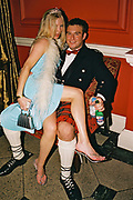 Coquettish woman wearing a tiara and feather boa sitting on the knee of a man wearing a kilt and Scottish national dress, at Posh at Addington Palace, UK, August, 2004