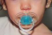 Baby with pacifier in her mouth = Model Release Available