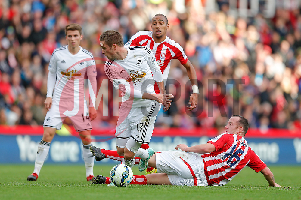 Gylfi Sigurosson of Swansea City is challenged by Charlie Adam of Stoke City - Photo mandatory by-line: Rogan Thomson/JMP - 07966 386802 - 19/10/2014 - SPORT - FOOTBALL - Stoke-on-Trent, England - Britannia Stadium - Stoke City v Swansea City - Barclays Premier League.