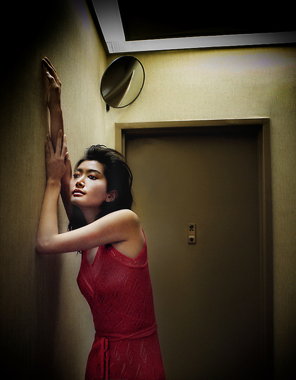 Young Japanese woman in red dress waits in apartment building hallway.