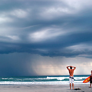 Surfers watch a storm pass, trying to decide if it was safe to get in the water after there were lightning strikes in the area.