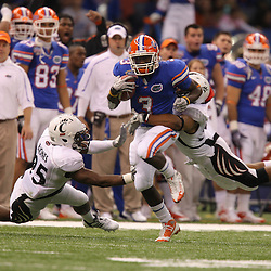 Jan 01, 2010; New Orleans, LA, USA; Florida Gators running back Chris Rainey (3) runs as Cincinnati Bearcats linebacker Andre Revels (right) and cornerback Brad Jones (left) converge on the tackle during the first half of the 2010 Sugar Bowl at the Louisiana Superdome.  Mandatory Credit: Derick E. Hingle-US PRESSWIRE.