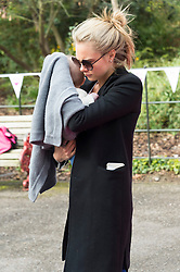 © Licensed to London News Pictures. 23/04/2016. CARA DELEVINGNE carrying a baby before she takes part in the inaugural Lady Garden 5km Run.  London, UK. Photo credit: Ray Tang/LNP