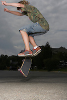 Teenage boy (16-17) jumping on skateboard on street side view