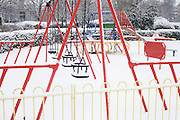 Bright colours and lines of a closed childrens' play park which lies in freshly-fallen snow.