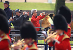 Tourists take photos of the Major General's Review, the rehearsal of the Trooping the Colour, the Queen's annual birthday parade, on The Mall, central London.