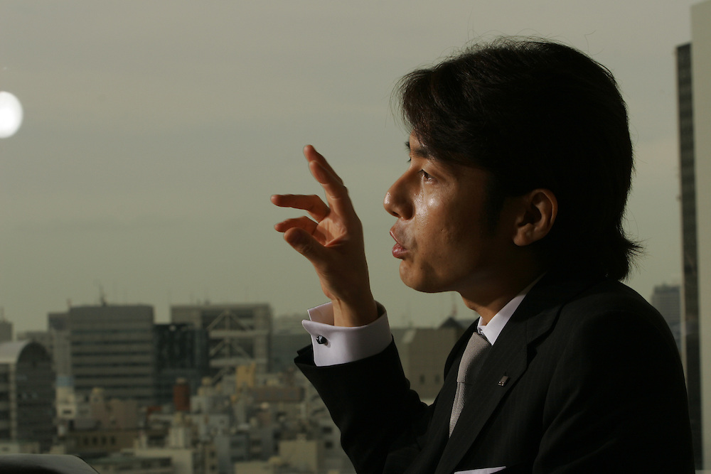 """Masatoshi Kumagai CEO of GMO Internet. A successful Japanese companyRecently Listed on the Tokyo Stock Exchange, that made its motto """"Internet for Everyone"""" at a time when other companies were focusing on much narrower strategies. Mr. Kumangi has built up an Internet empire that does everything from Web hosting to media. It seems to work. He claims to have developed a methodology that allows the company to identify viable web-related markets...He is being photographed in is offices and while giving a talk to selectedemployees of the brokerage firm, Marusan Securities. (board room situatio"""