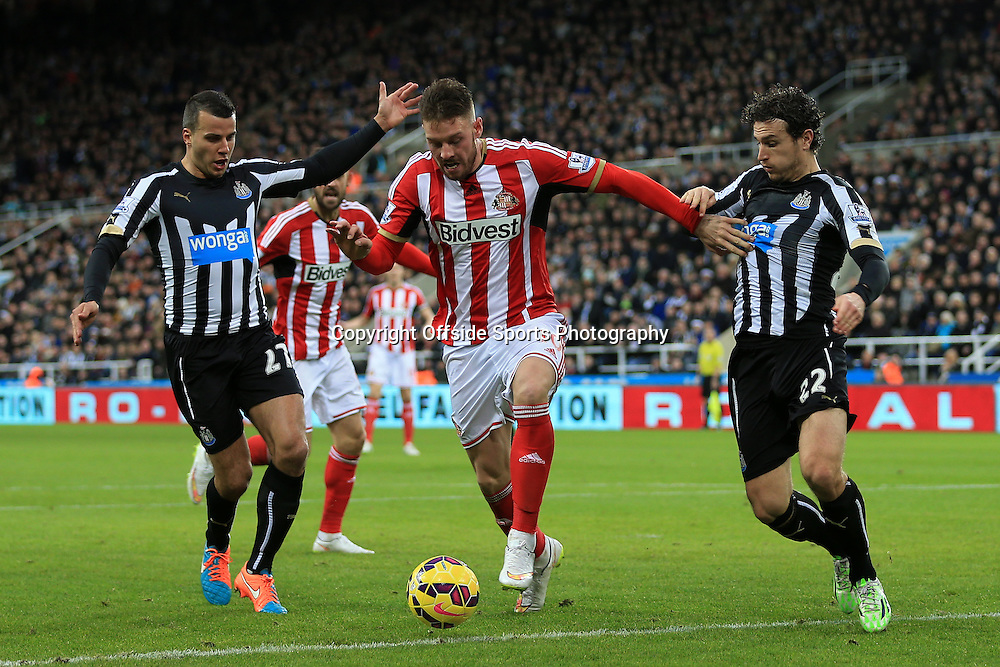 21st December 2014 - Barclays Premier League - Newcastle United v Sunderland - Connor Wickham of Sunderland battles with Steven Taylor of Newcastle (L) and Daryl Janmaat of Newcastle - Photo: Simon Stacpoole / Offside.