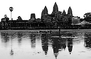 Angkor Wat, built during the early years of the 12th century by Suryavaram II, honors the Hindu god Vishnu and is a symbolic representation of Hindu cosmology. Consisting of an enormous temple symbolizing the mythic Mt. Meru, its five inter-nested rectangular walls and moats represent chains of mountains and the cosmic ocean. The short dimensions of the vast compound are precisely aligned along a north-south axis, while the east-west axis has been deliberately diverted 0.75 degrees south of east and north of west, seemingly in order to give observers a three day anticipation of the spring equinox.  Angkor was forgotten for a few centuries. Wandering Buddhist monks, passing through the dense jungles, occasionally came upon the awesome ruins. Recognizing the sacred nature of the temples but ignorant of their origins, they invented fables about the mysterious sanctuaries, saying they had been built by the gods in a far ancient time. Centuries passed, these fables became legends, and pilgrims from the distant reaches of Asia sought out the mystic city of the gods.<br /> European visitors to Cambodia towards the later end of this period were intrigued by the &quot;lost city&quot; of Angkor. After the French established a colonial regime in Cambodia in 1863, the entire site became a focus of scholarly interest.