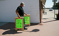 Larry Wells carries signs advertising eclipse t-shirts for sale in Guernsey, Wyoming U.S. August 20, 2017.  REUTERS/Rick Wilking