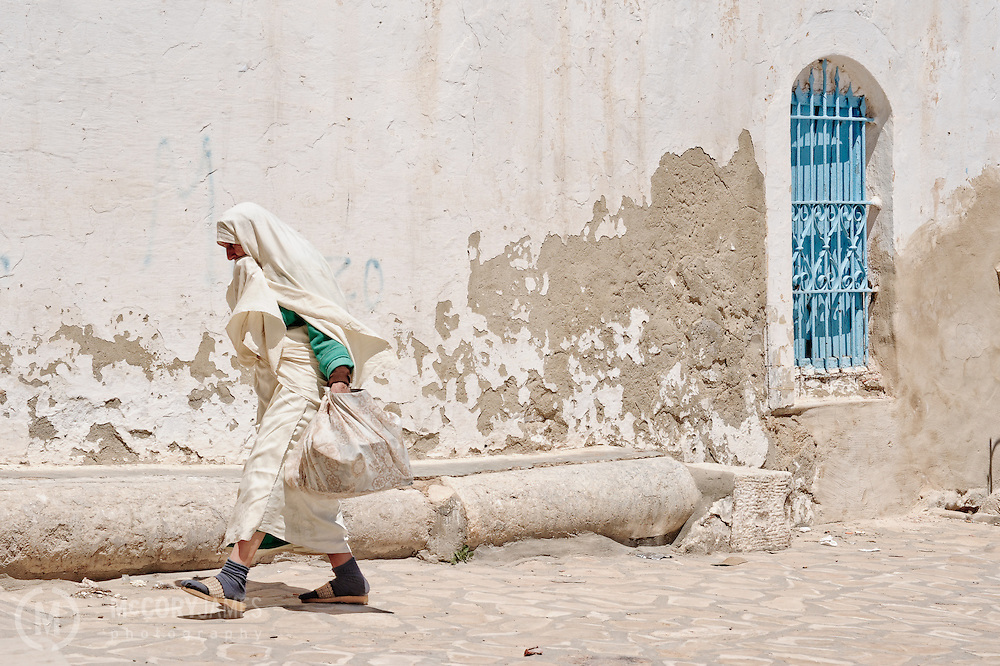 A Tunisian woman walks from the market in Tabersouk, Tunisia
