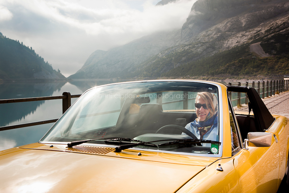 27 August 2010. Passo Fedaia, Trentino Alto Adige, Italy. ADAC reporter Katja Fastrich drives a Porsche 914-6  by the Lake Fedaia, in Passo Fedaia. Passo Fedaia (2.057 m) is a high mountain pass in the Italian Alps formed of a 2,5km plateau in which the artificial Lake Fedaia is used for Hydropower. One hundred vintage cars participated at the ADAC Trentino Oldtimer-Wanderung.<br /> <br /> <br /> &copy;2010 Gianni Cipriano<br /> cell. +1 646 465 2168 (USA)<br /> cell. +39 328 567 7923<br /> gianni@giannicipriano.com<br /> www.giannicipriano.com