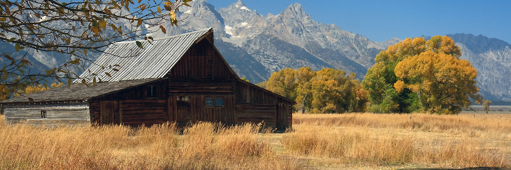 The mountains of the Grand Tetons loom behind a barn at a historic Mormon homestead.