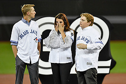 March 29, 2018 - Toronto, ON, U.S. - TORONTO, ON - MARCH 29: Roy Halladay's family, son Braden (L), wife Brandy and other son Ryan take in the emotion during a ceremony honoring the late pitcher by retiring his No. 32 on opening day before the MLB season game between the New York Yankees and the Toronto Blue Jays at Rogers Centre in Toronto, ON., Canada March 29, 2018. Jays players will also wear a no. 32 patch on their jerseys throughout the season in tribute to Halladay. Halladay, nicknamed 'Doc' who spent 12 seasons as a pitcher with the Jays, died in November 2017 when his personal plane crashed into the Gulf of Mexico near Tampa. He was 40 years old. Halladay joins Robero Alomar (no. 12) as the only 2 players in Jays history to have their jersey numbers retired. (Photo by Jeff Chevrier/Icon Sportswire) (Credit Image: © Jeff Chevrier/Icon SMI via ZUMA Press)