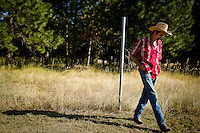 Errold Asbury walks along his property line Thursday on Borley Road. Kootenai County has labeled his property as a wrecking yard which Asbury contends he only has three vehicles on his property and the view from the roadway shows nothing to support the county's claim.