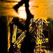 A passerby walks past a puddle reflecting some of the detail of the Eiffel Tower at night.