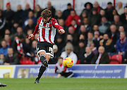 Brentford midfielder John Swift fires in a shot during the Sky Bet Championship match between Brentford and Brighton and Hove Albion at Griffin Park, London, England on 26 December 2015.