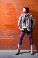 Teenage girl (16-17) leaning on brick wall