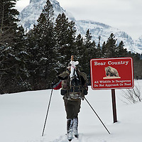 man skiing with deer leg on back in front of grizzly bear sign, glacier national park, montana
